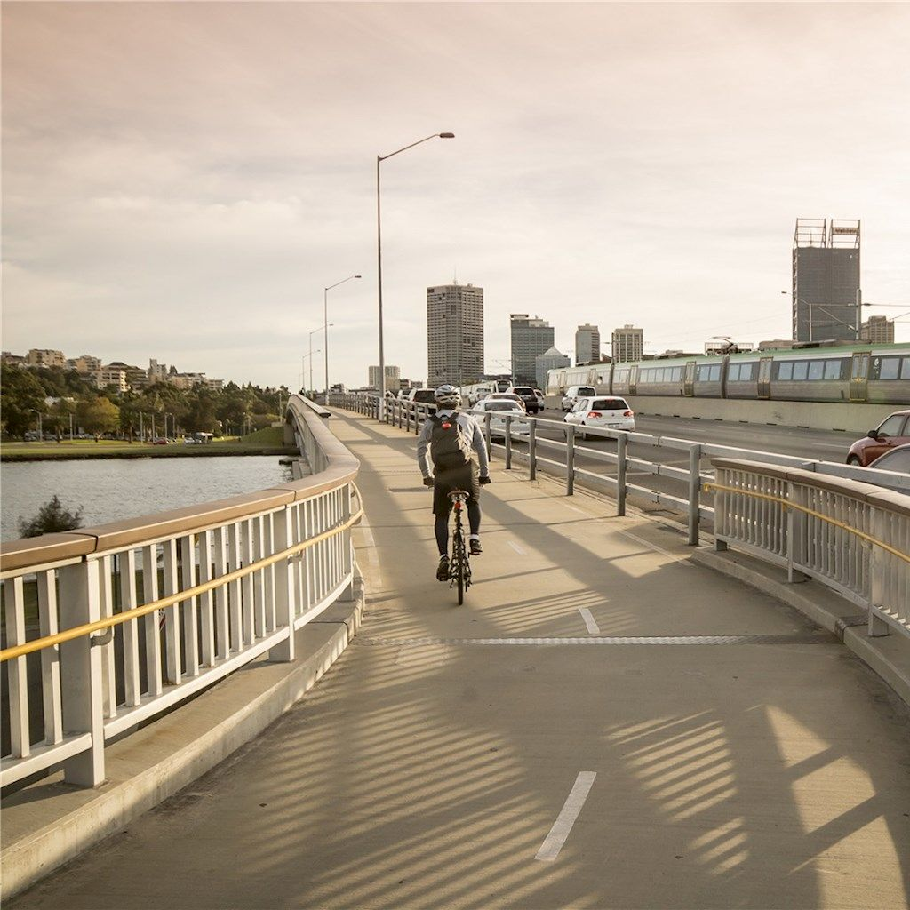 Cyclist riding on a path next to the freeway